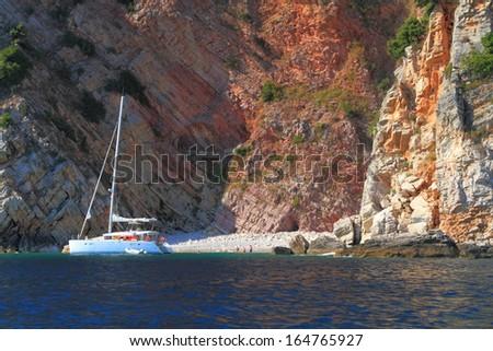White catamaran near small beach on the shores of Adriatic sea - stock photo