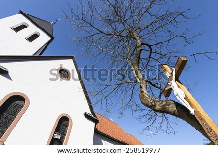 white catholic church and a wooden ross with a crucified Jesus statue under a tree without leaves, Germany, Europe - stock photo