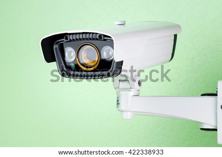white CCTV security camera on green wall. - stock photo
