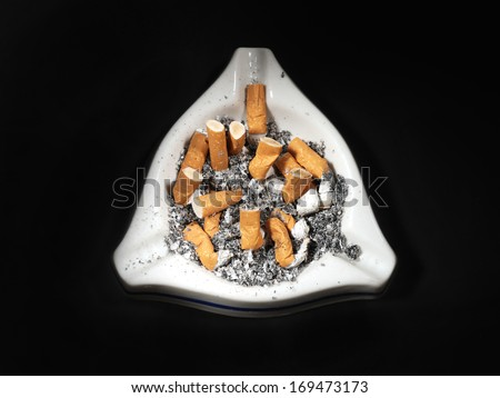 White ceramic ash tray full of cigarette butts on black background - stock photo
