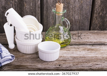 White ceramic baking dish, measuring spoons for baking and a bottle with olive oil on a simple wooden background. The concept is simple home cooking with family recipes. Selective focus, horizontal - stock photo