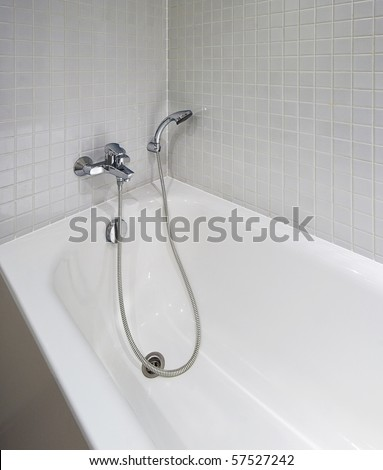 white ceramic bath tub with shower attachment and mozaic tiles - stock photo