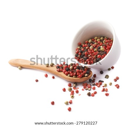 White ceramic cup filled with the multiple red, black and green pepper seeds next to the wooden spoon, composition isolated over the white background - stock photo