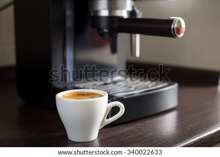 White ceramic cup of espresso with coffee ma?hine on the table. Brewing coffee at work - stock photo