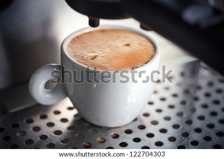 White ceramic cup of fresh espresso with foam in the coffee machine. - stock photo