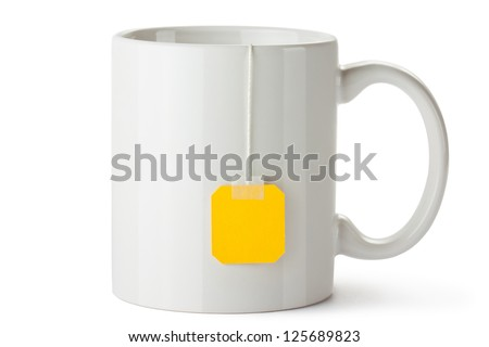 White ceramic mug with teabag label. Isolated on a white. - stock photo
