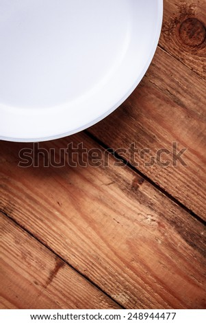 White ceramic pan with a black pen on the old wooden table. top view - stock photo