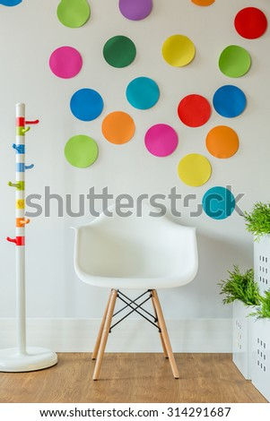 White chair and color spots on wall in child's room - stock photo