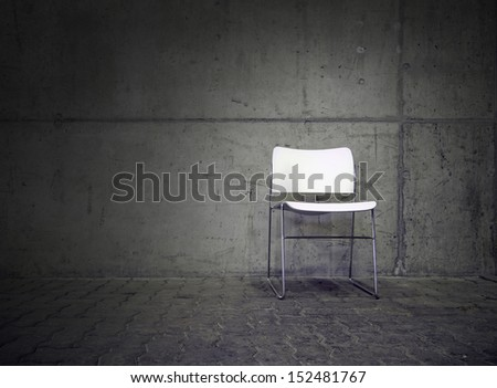 white chair in spotlight with concrete wall in the background - stock photo