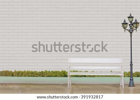 white chair with street electric lamp post and green grass at white brick wall - stock photo