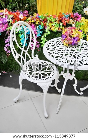 White chairs in the flowers garden - stock photo