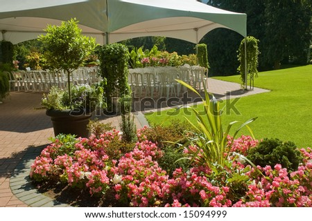White chairs set up for an outdoor wedding in a garden - stock photo