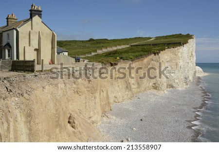 White Chalk Cliffs the Seven Sisters at Birling Gap near Eastbourne in East Sussex. England. With houses close to cliff edge in danger of collapse - stock photo