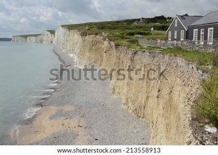 White Chalk Cliffs the Seven Sisters at Birling Gap near Eastbourne in East Sussex. England. With cafe on cliff top - stock photo