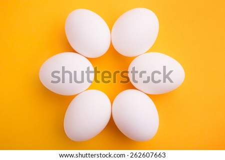 White chicken eggs on a yellow background - stock photo