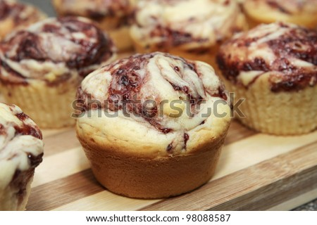 white chocolate and raspberry flavored muffin on a cutting board - stock photo