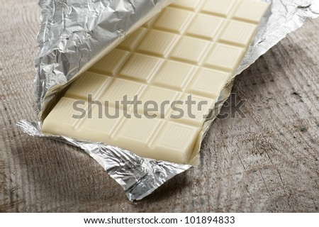 white chocolate bar in aluminum foil, on wood table - stock photo