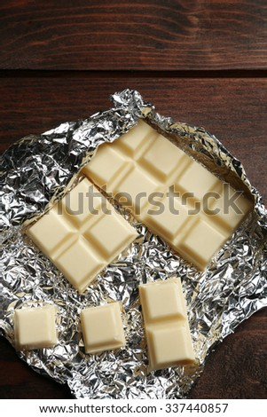 White Chocolate bar in foil, close-up, on wooden background - stock photo