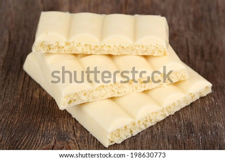 White chocolate bar on color wooden background - stock photo