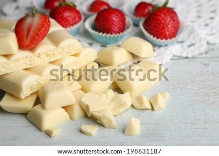 White chocolate bar with fresh strawberries, on color wooden background - stock photo