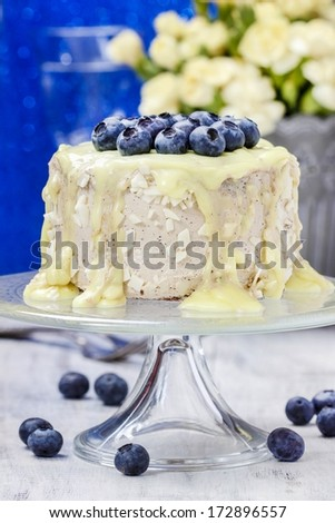 White chocolate cake decorated with blueberries. Bouquet of yellow carnations in the background - stock photo