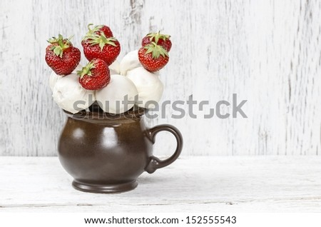 White chocolate cake pops and strawberries on sticks. Birthday party dessert on wooden background. - stock photo