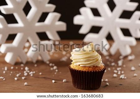 White chocolate cupcake on white snow flakes Christmas background - stock photo