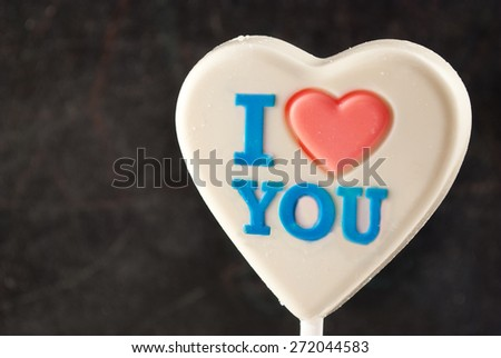 """White chocolate heart with """"I love you"""" colorful inscription. - stock photo"""