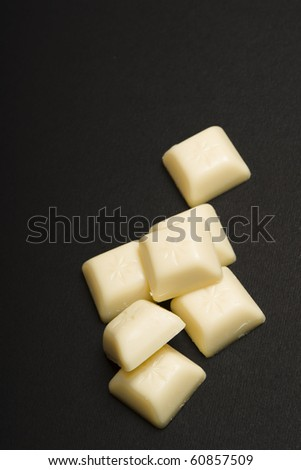 White chocolate on black background. - stock photo