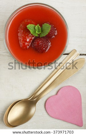 White chocolate panna cotta with raspberries and strawberries, two golden spoons and pink heart on white background - stock photo