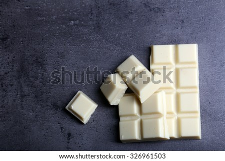 White chocolate pieces on gray background - stock photo