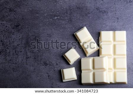 White chocolate pieces on gray background - stock photo