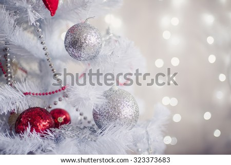 White Christmas decoration with balls on fir branches with blurred background - stock photo