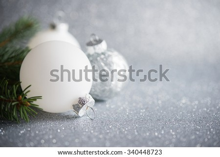 White christmas ornaments on silver glitter background with space for text. Merry christmas card. Winter holidays. Xmas theme. Happy New Year. - stock photo