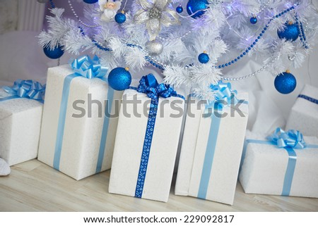 White Christmas tree with a blue toy, garlands, beads, boxes, gifts - stock photo