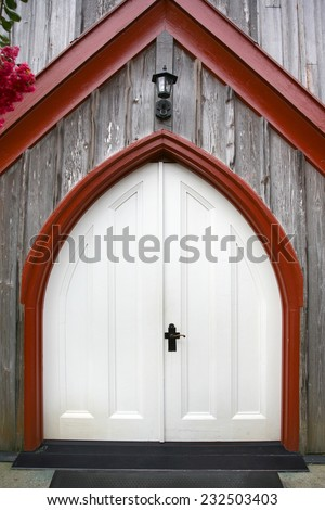 white church door with red trim and unique shape dark handle - stock photo