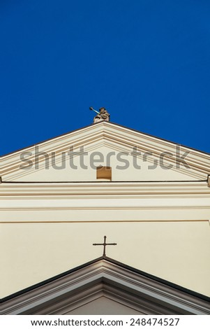 White church wall with a statue and cross on it - stock photo