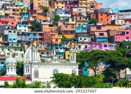 White church with a colorful slum on a hill rising above it in Guayaquil, Ecuador - stock photo
