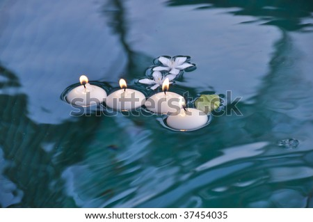 White Circle Candles with Fire on Water - stock photo