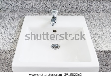 White clean basin on the marble top of the bathroom. - stock photo