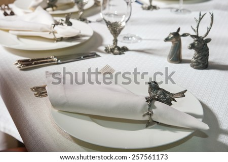 White clean plate with a napkin on which to lay the table covered with a white tablecloth - stock photo