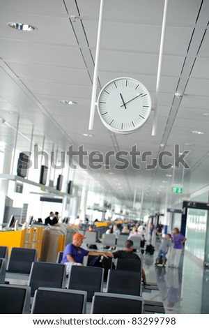 White clock in a waiting lounge in an airport terminal with people sitting in the background - stock photo