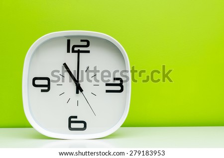white clock on light green background - stock photo