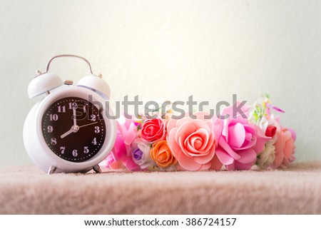 White clock with flowers on a table in muted vintage retro style. - stock photo