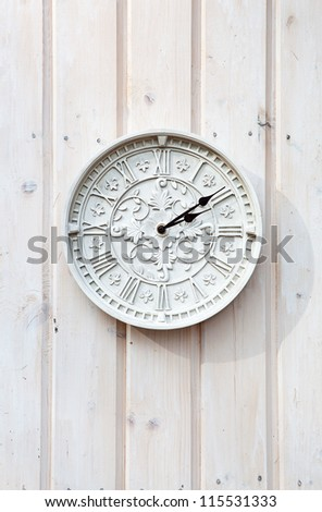 White clock with vintage decoration on a wooden wall - stock photo