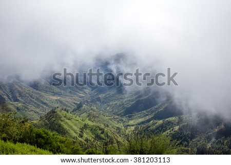 White clouds above the green mountains on La Gomera island in Spain. Wide angle image with copy space - stock photo