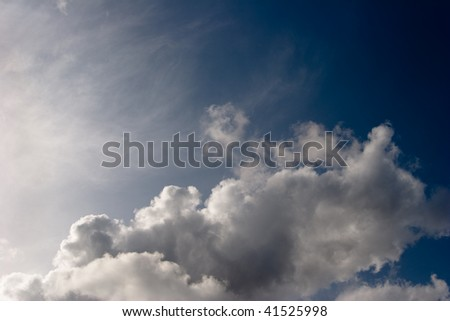 White clouds against stormy dark sky - stock photo