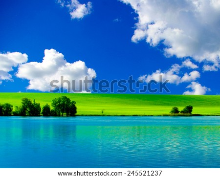 white clouds and a green field - stock photo