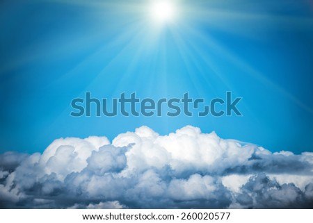White clouds and bright sun on the blue sky. Nature background - stock photo