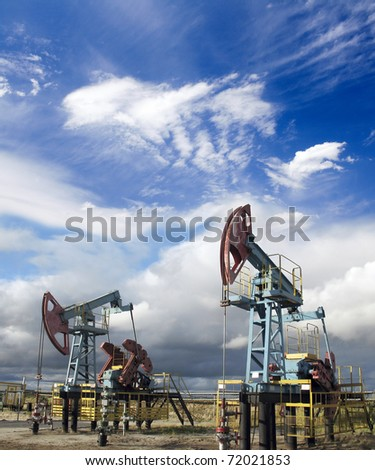 White clouds and oil pumps. Industrial scene - stock photo